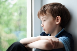 a child quietly sits by the window and looks out into the backyard