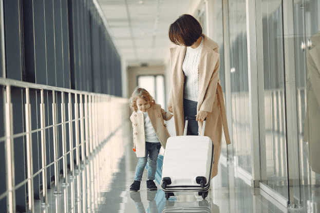 Woman holding lugging with one hand and holding hands with a young girl with the other in an airport.
